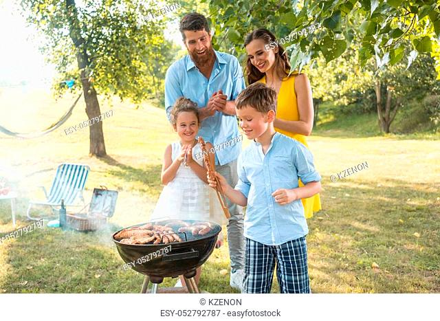 Portrait of a happy family with two cute children, a boy and a girl, looking at camera while standing outdoors near the barbecue grill on a green hill in summer