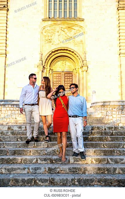 Two tourist couples on church stairway, Calvia, Majorca, Spain
