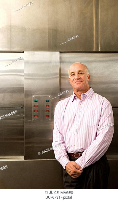 Male restaurant manager standing in commercial kitchen, smiling, portrait