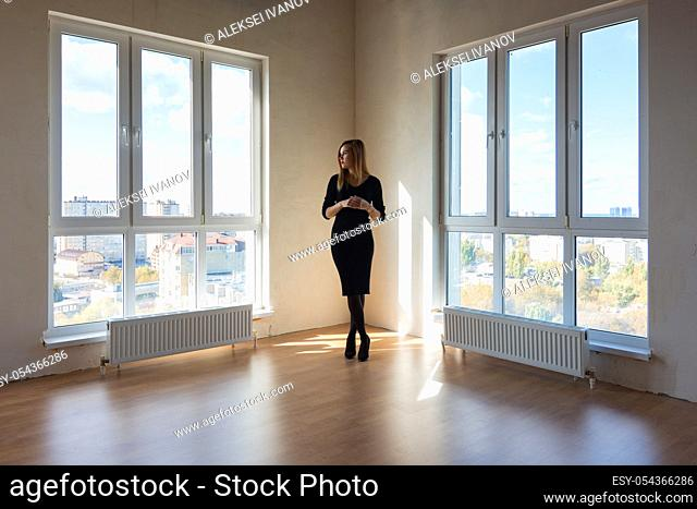 A girl in a black dress stands between two large windows in a spacious empty apartment