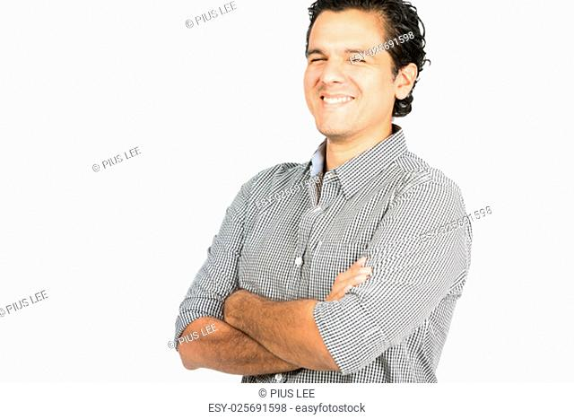 A good looking latino male wearing collared button down shirt laughing with arms crossed looking at the camera showing easy going, warm, friendly, positive