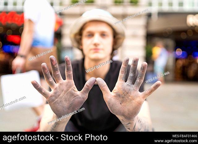 Street art, pavement artist showing his dirty hands