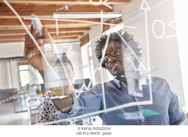 Business people drawing graph on window in office