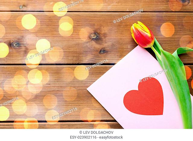 holidays, love and valentines day concept - close up of tulip flowers and greeting card with heart on wooden table