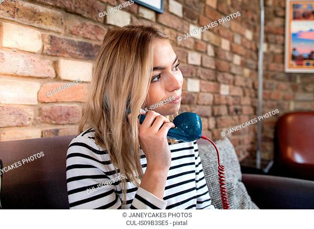 Young woman sitting at home, using telephone