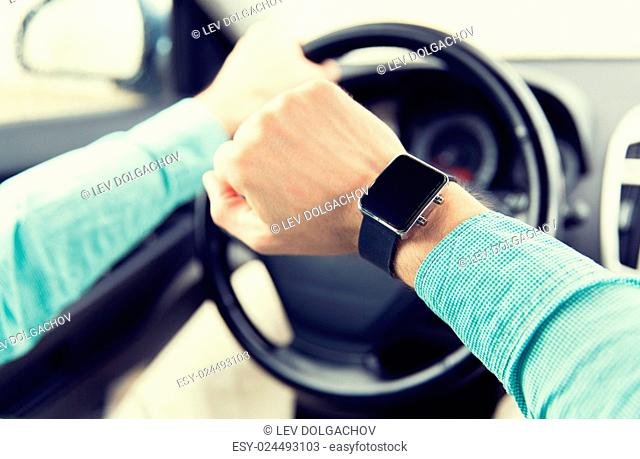 transport, business trip, technology, time and people concept - close up of man with wristwatch driving car