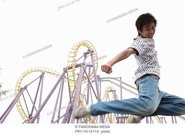 Portrait of young man jumping at amusement park, smiling