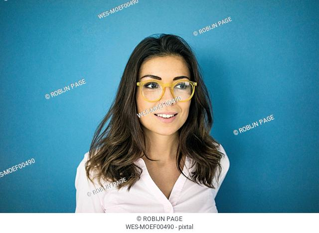 Portrait of smiling woman wearing glasses in front of blue background
