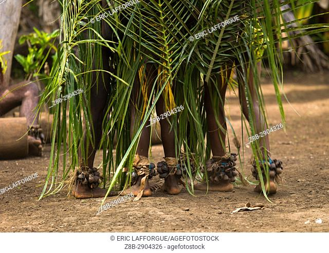Small Nambas children covered with palm leaves dancing in front of slit gong drums during the palm tree dance, Malekula island, Gortiengser, Vanuatu