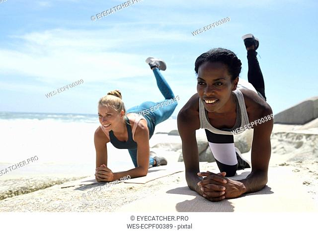 Two women doing a fitness exercise on the beach