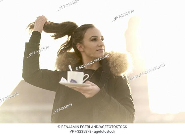 woman holding pigtail hair style and coffee cup, outdoors in city next to Frauenkirche, Marienkirche, in Munich, Germany