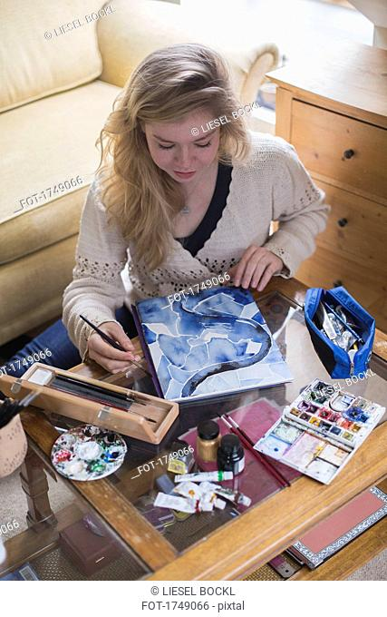 High angle view of young woman making painting while sitting in living room