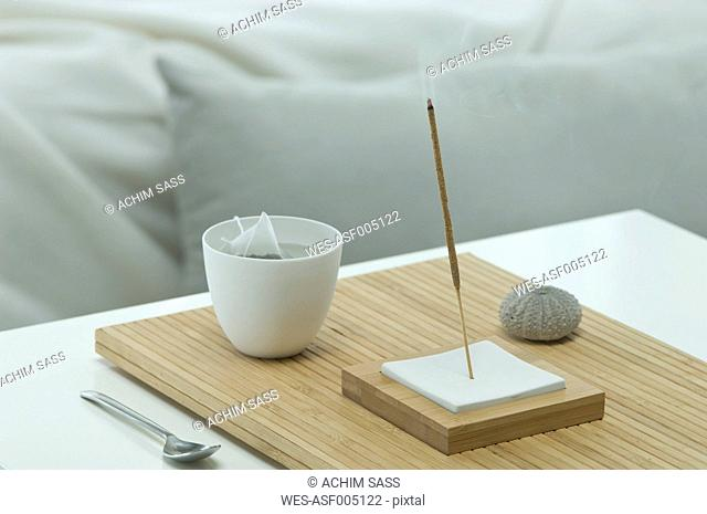 Aromatheraphy, tea, scent, aroma sticks, sea urchin shell, with a bed visible in the backgroud, studio