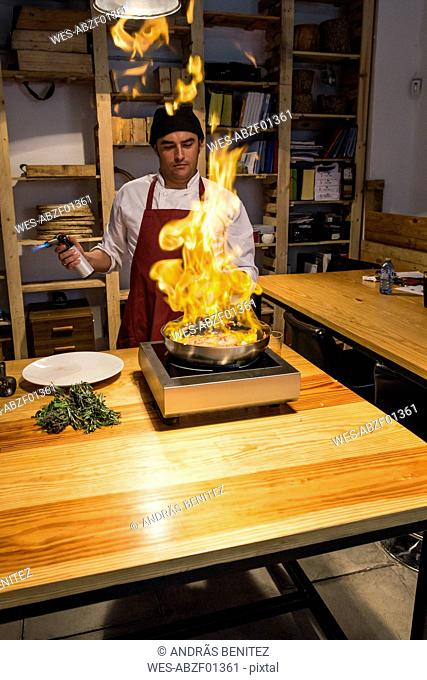 Man flambing beef cheeks with sauteed vegetables in a pan using a kitchen torch