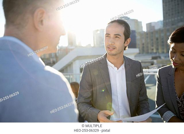 Business people discussing paperwork on sunny urban rooftop