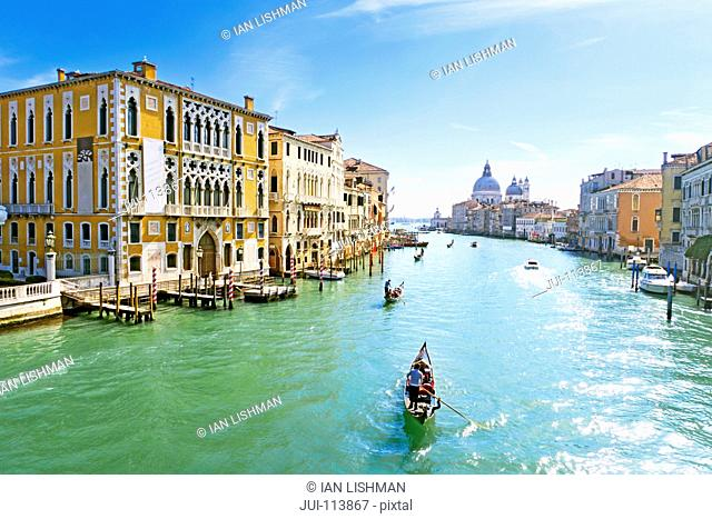 Gondoliers paddling tourists in gondola among architectural buildings in sunny Grand Canal in Venice, Italy