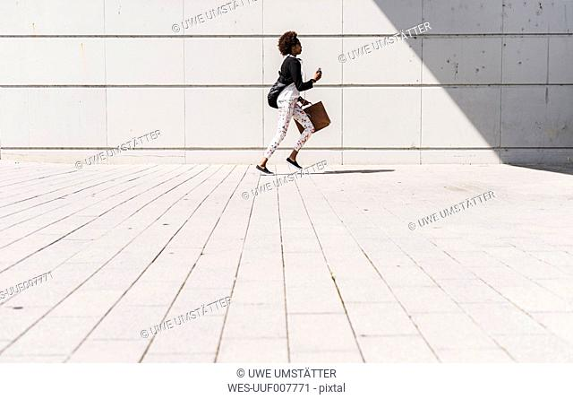 Running businesswoman with smartphone and briefcase