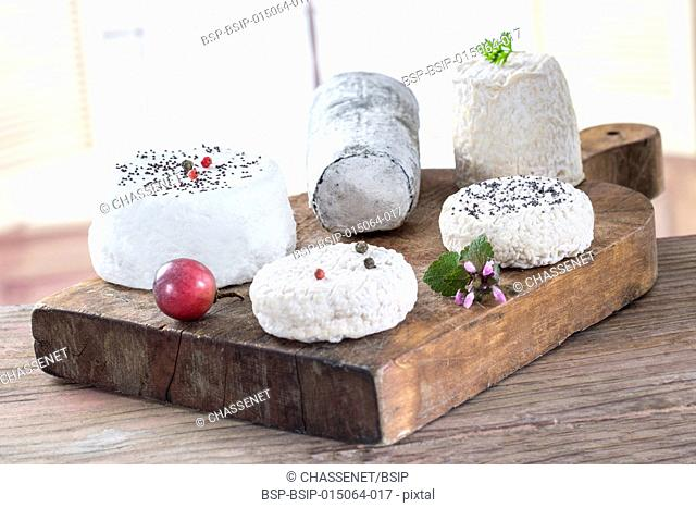 Various french goat cheese on wooden board