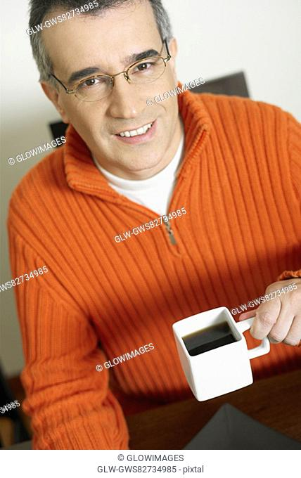 Portrait of a mid adult man holding a cup of coffee