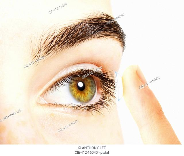 Extreme close up of woman putting contact lens into eye
