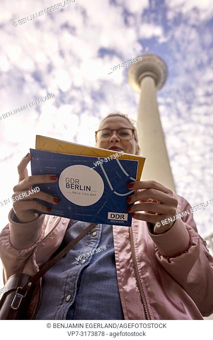 Woman with city tour guide maps under Fernsehturm, in Berlin, Germany