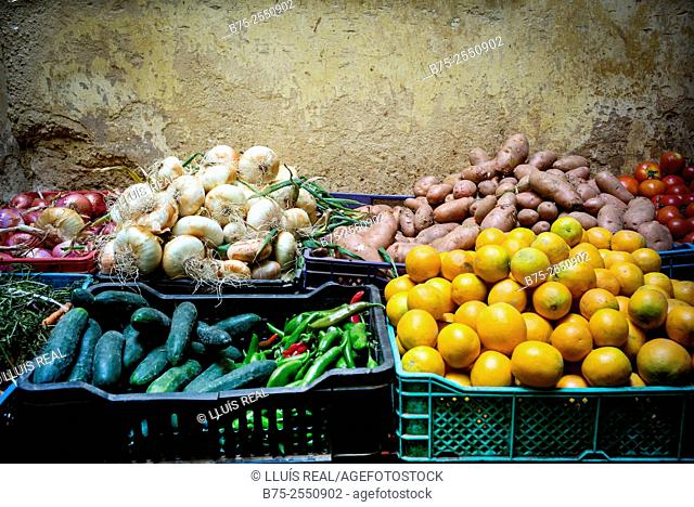Drawers with organic products, onions, potatoes, tomatoes, cucumbers, peppers and oranges in the street market in the medina of Fez, Morocco, Africa