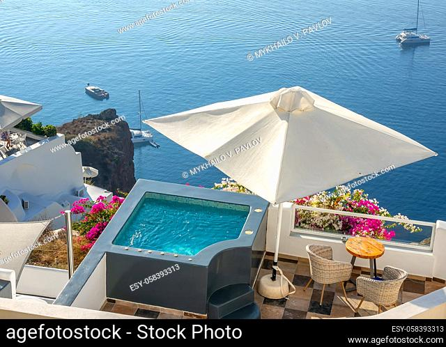 Santorini. Terraces on the high shore of Thera Island. Swimming pool and loungers for relaxing in sunny weather. Yachts by the shore