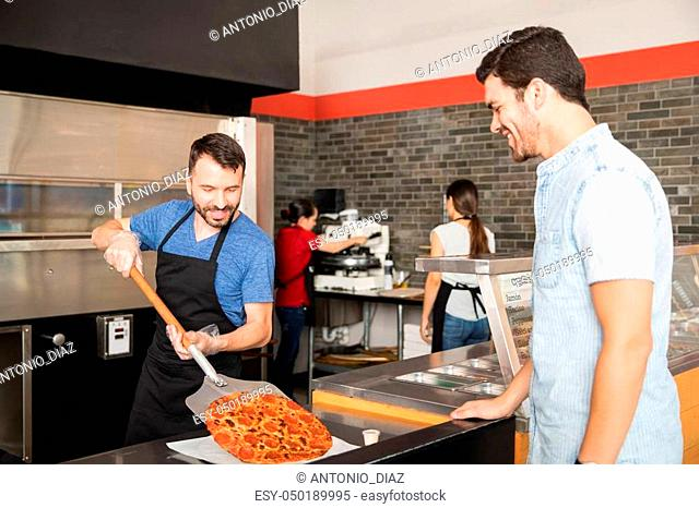 Handsome man smiling looking at freshly baked pizza order which is being put on serving plate by chef using a peel in restaurant kitchen counter