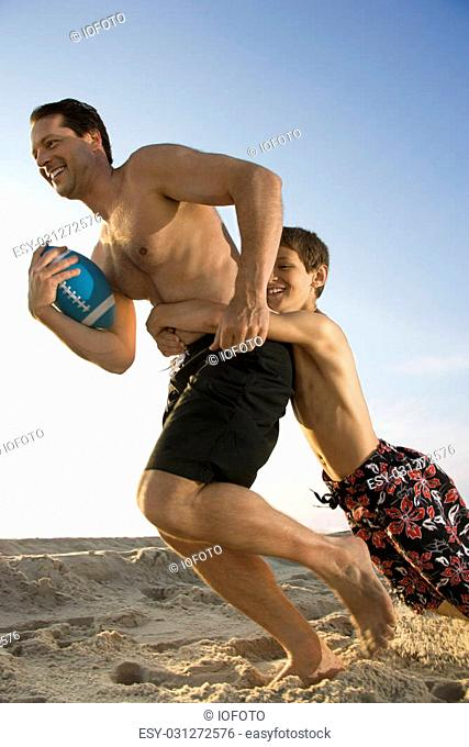 Caucasian mid-adult man running with football being tackled by pre-teen boy