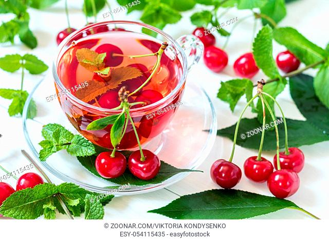Fresh fruit cherry drink in transparent glass cup surrounded by cherries on the white wooden background
