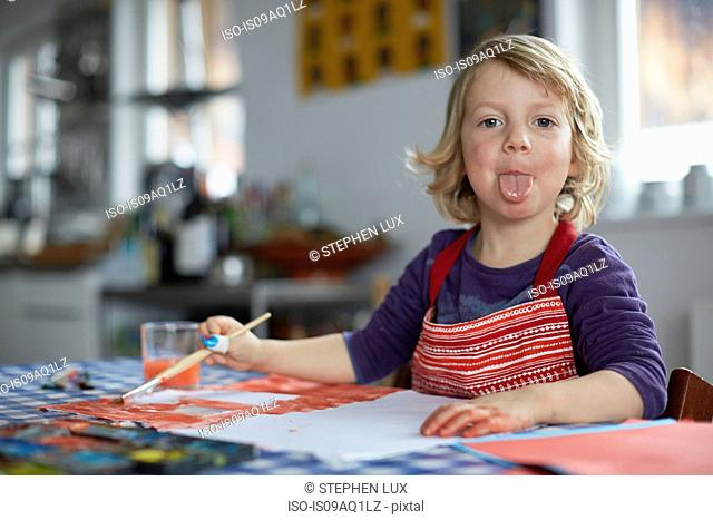 Portrait of young boy sitting at table, holding paintbrush, poking tongue out