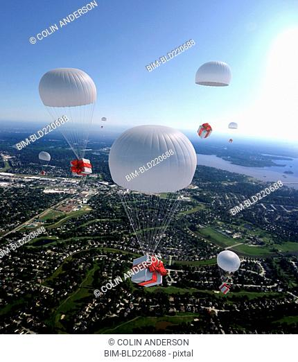 High angle view of gifts parachuting over suburban cityscape