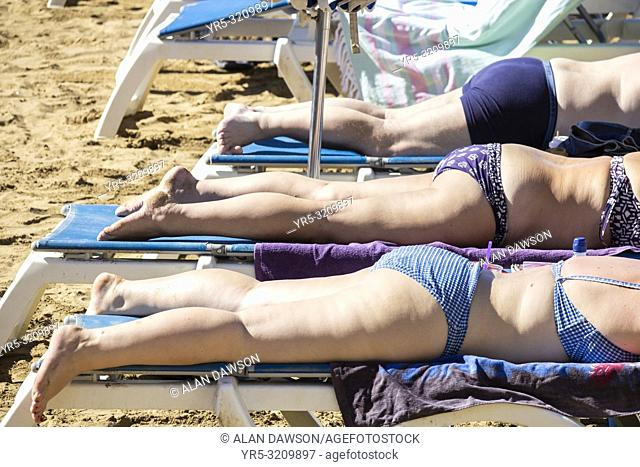 Two women and a man sunbathing on beach on Gran Canaria, Canary Islands, Spain
