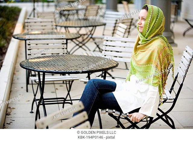 Young woman wearing a head scarf sitting at a table