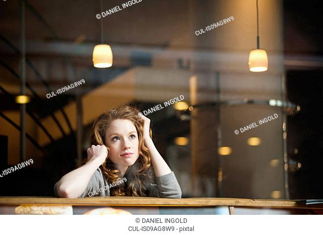 Thoughtful young woman sitting alone in cafe