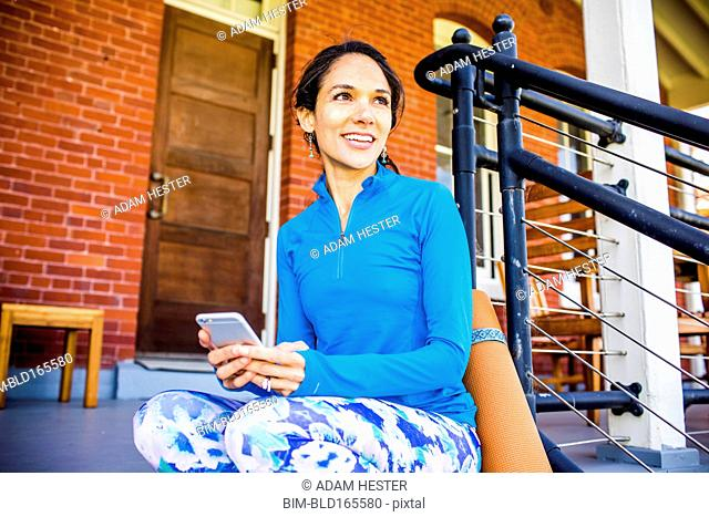 Hispanic woman using cell phone on porch