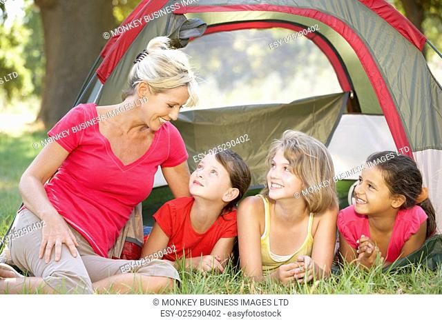Group Of Girls With Mother Having Fun In Tent In Countryside