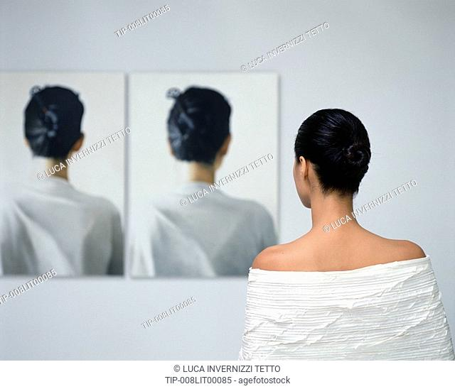 Woman looking at her own portraits