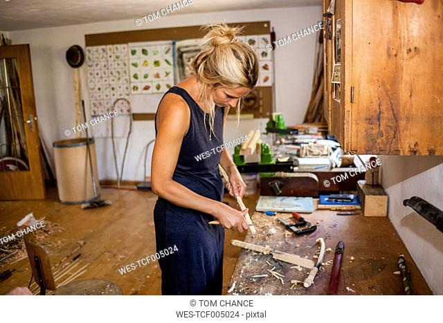 Woman in workshop working on Stone-Age spear-thrower