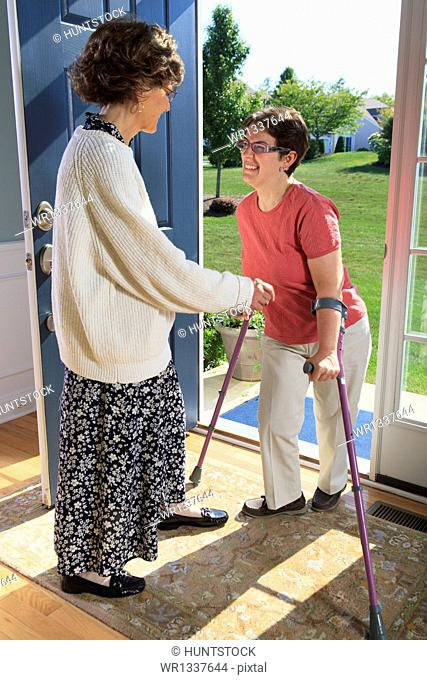 Woman with cerebral palsy greeting someone at the door