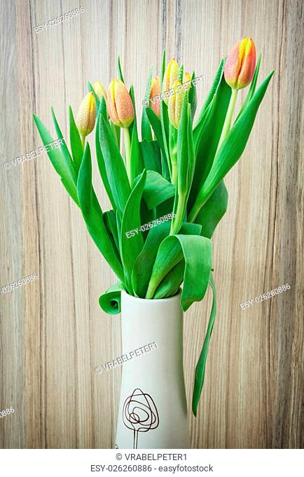 Bouquet of orange tulips in the vase on the wooden background. Gift of love. Beautiful seasonal cut flowers. Vertical composition