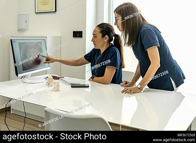 Female doctors discussing while looking at x-ray in dentist's office
