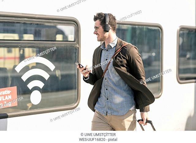 Smiling young man with headphones and cell walking along train with wifi symbol