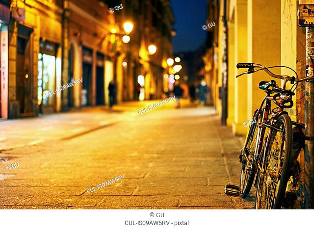 Bicycle leaning against street wall at night, Bologna, Italy
