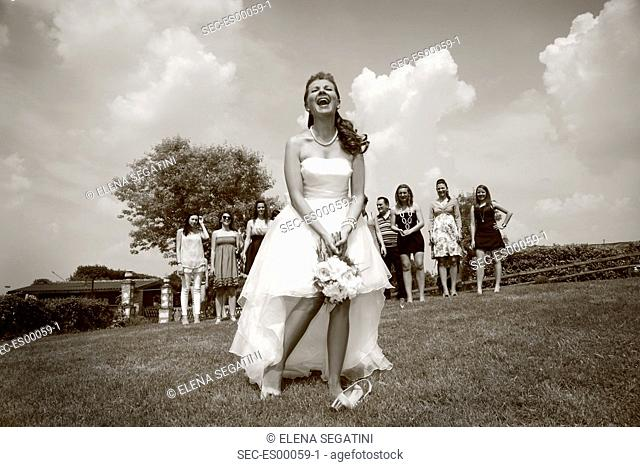 Italy, Venice, Mirano, Bride standing on meadow, wedding guests in background