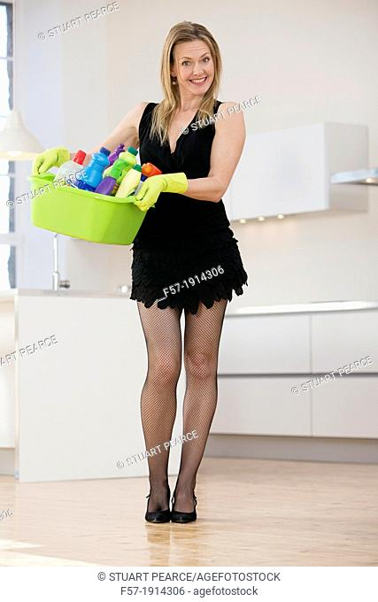 Domestic goddess holding cleaning products in her kitchen