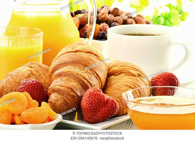 Breakfast with croissants, cup of coffee and fruits