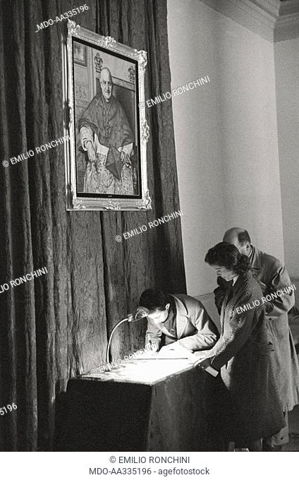 Believers signing some papers. Some believers signing some papers on a table. Above them, a painting of Cardinal Angelo Roncalli. Venice, 1950s
