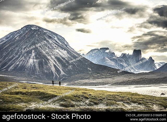Silhouette of two backpackers hiking through dramatic mountain pass