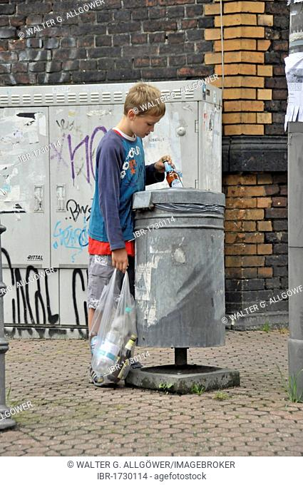Nine year old boy earning his pocket money by collecting returnable bottles, Germany, Europe